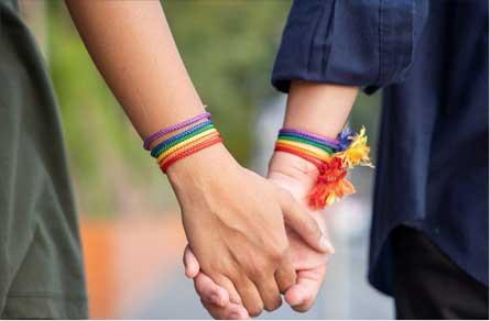 Two people holding hands wearing pride bracelets.