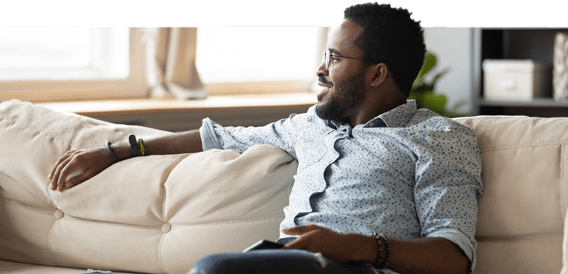 A smiling man on a couch discussing faith transitioning